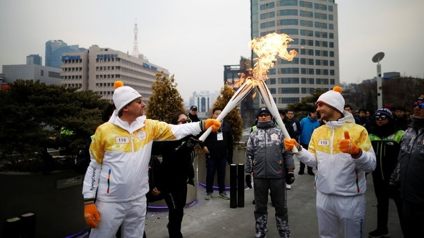 Torchbearers carry Olympic torches in Seoul, South Korea, January 13, 2018.  REUTERS/Kim Hong-Ji - RC11F1F03660