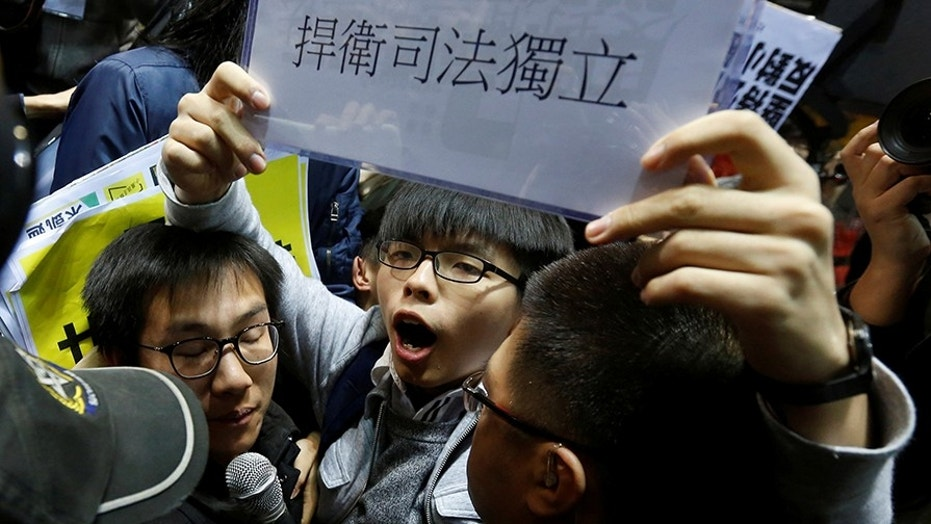 "Student leader Joshua Wong shouts and holds up a sign reading ""defend judicial independence"" during a confrontation with security guards at a news conference held by former Chief Secretary and Chief Executive election candidate Carrie Lam in Hong Kong, China February 27, 2017.      REUTERS/Bobby Yip     TPX IMAGES OF THE DAY - RC13C613DA10"