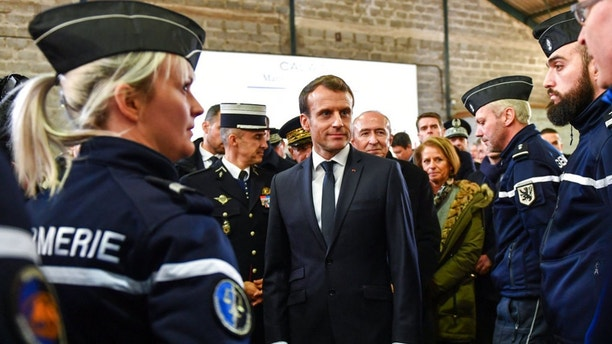 "French President Emmanuel Macron, center, speaks with French gendarmes during his visit to Calais, northern France, Tuesday, Jan.16, 2018. Macron traveled Tuesday to the epicenter of France's migrant crisis, the northern port of Calais, to lay out a ""humane and tough"" immigration policy that involved better behavior by security forces and closer cooperation with Britain. (Denis Charlet/Pool via AP)"