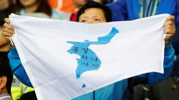 A spectator holds a pro-unification flag with the Korean peninsula on it before the start of the gold medal match between North Korea and South Korea at Munhak Stadium during the 17th Asian Games in Incheon October 2, 2014.  REUTERS/Kim Kyung-hoon  (SOUTH KOREA - Tags: SPORT SOCCER) - GM1EAA21KBQ01