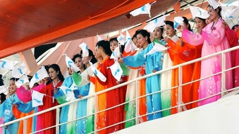 "North Korean women dressed in traditional robes wave ""Unification"" flags on the deck as their ferry arrives at the Dadaepo port in Busan, September 28, 2002. A North Korean group of 368 supporters arrived to cheer their athletes during the 14th Asian Games, which begin here on Sunday. REUTERS/Ahn Young-joon/Pool  AHN CHI - RP3DRIEUQDAA"