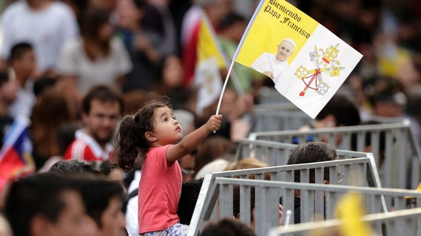 A young girl hods up a Papal welcome flag as she waits to get a glimpse of Pope Francis upon his arrival in Santiago, Chile, Monday, Jan. 15, 2018. (AP Photo/Victor R. Caivano)