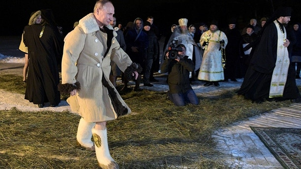Russian President Vladimir Putin walks to take a dip in the water during Orthodox Epiphany celebrations at lake Seliger Tver region Russia