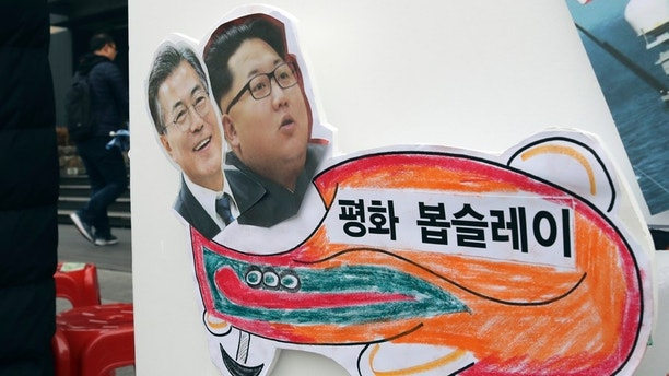 "In this Tuesday, Jan. 16, 2018, photo, pictures of South Korean President Moon Jae-in, left, and North Korean leader Kim Jong Un are seen on a sign during a rally for a peaceful Winter Olympics in Seoul, South Korea. North Korea plans to send a spotlight-stealing delegation to next month's Winter Olympics in the South Korean county of Pyeongchang. The letters read ""Peace bobsleigh."" (AP Photo/Lee Jin-man)"