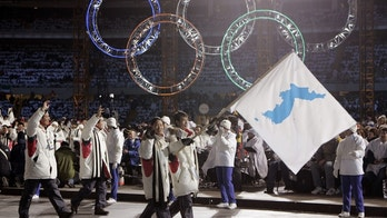 FILE - In this Feb. 10, 2006, file photo, Korea's flag-bearers Bora Lee and Jong-In Lee, carrying a unification flag lead their teams into the stadium during the 2006 Winter Olympics opening ceremony in Turin, Italy. When athletes of the rival Koreas walked together behind a single flag for the first time since their 1945 division at the start of the 2000 Sydney Olympics, it was a highly emotional event that came on the wave of reconciliation mood following their leaders' first-ever summit talks. Eighteen years later, now, the Koreas are pushing to produce a similar drama during the upcoming Pyeongchang Olympics. But they haven't generated as much enthusiastic supports as they had both at home and abroad. (AP Photo/Amy Sancetta, File)