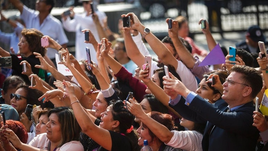 A crowd of people aiming phones at Pope Francis as he arrives for a mid-morning prayer in Lima, Peru, on Sunday.
