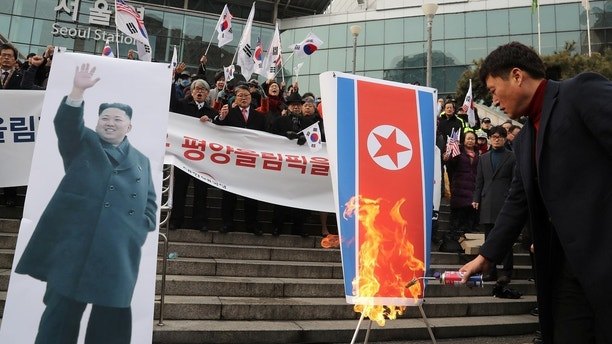 A member of a South Korean conservative civic group burns a North Korean national flag during a protest opposing North Korea's participation in the 2018 Pyeongchang Winter Olympics, in Seoul, South Korea, January 22, 2018.   Yonhap via REUTERS   ATTENTION EDITORS - THIS IMAGE HAS BEEN SUPPLIED BY A THIRD PARTY. SOUTH KOREA OUT. NO RESALES. NO ARCHIVE. - RC1DAB9FD900