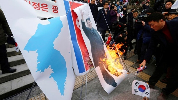"South Korean protesters burn a portrait of North Korean leader Kim Jong Un during a rally against a visit of North Korean Hyon Song Wol, head of North Korea's art troupe, in front of Seoul Railway Station in Seoul, South Korea, Monday, Jan. 22, 2018. ""Executed"" North Korean pop diva takes Olympic spotlight, but Hyon was met at Seoul railway station by about 150 to 200 activists. The demonstrators later burned Kim's photo, a North Korean flag and a ""unification flag"" the rival Koreas plan to carry during the opening ceremony. (AP Photo/Ahn Young-joon)"