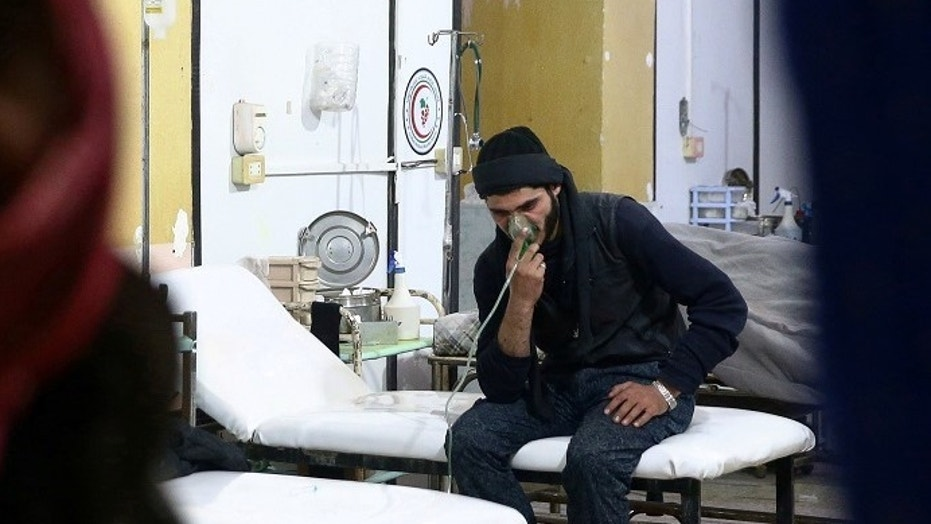 A man breathes through an oxygen mask at a medical center in Douma in Damascus, Syria.