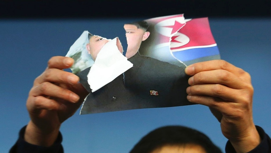 North Korean defector Park Sang-hak holds up a defaced portrait of North Korean leader Kim Jong Un during a news conference against North Korea's participation in next month's Winter Olympics, in Seoul, Jan. 24, 2018.