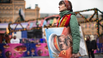 FILE - In this file photo taken on Thursday, Dec. 21, 2017, An artist holds a portrait of former Soviet leader Josef Stalin as communist party supporters marking the anniversary of Stalin's birth outside the GUM, State Department store decorated with New Year and Christmas illumination in Moscow's Red Square, Russia.  Russia's Culture Ministry  on Tuesday Jan. 23, 208 has banned the satirical film about Soviet dictator Josef Stalin's death two days before its scheduled release. (AP Photo/Alexander Zemlianichenko, File)