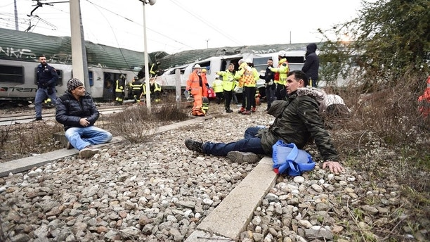 Rescue teams work on a derailed train at the station of Pioltello Limito, on the outskirts of Milan, Italy, Thursday, Jan. 25, 2018. Carabinieri say a commuter train carrying hundreds of people has derailed in northern Italy, killing at least two people and seriously injuring at least 10. (Flavio Lo Scalzo/ANSA via AP)