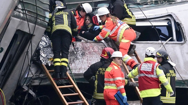 Firefighters help a woman out of the wagon of a derailed train at the station of Pioltello Limito, on the outskirts of Milan, Italy, Thursday, Jan. 25, 2018. Carabinieri say a commuter train carrying hundreds of people has derailed in northern Italy, killing at least two people and seriously injuring at least 10. (Flavio Lo Scalzo/ANSA via AP)