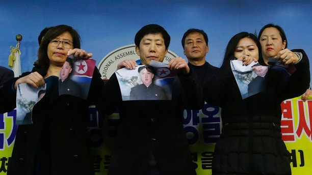 North Korean defectors tear portraits of North Korean leader Kim Jong Un during a press conference against the North Korea's participation in the 2018 Pyeongchang Winter Olympics at the National Assembly in Seoul, South Korea, Wednesday, Jan. 24, 2018. A team of South Korean officials travelled to North Korea on Tuesday to check logistics for joint events ahead of next month's Winter Olympics in the South, as the rivals exchanged rare visits to each other amid signs of warming ties. (AP Photo/Ahn Young-joon)