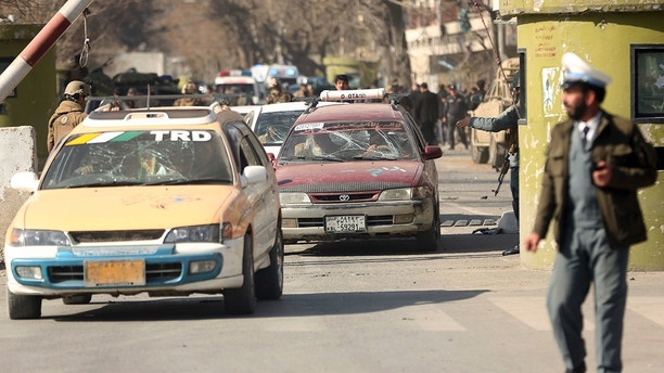 Security forces inspect at the site of a deadly suicide attack in the center of Kabul, Afghanistan, Saturday, Jan. 27, 2018. A suicide car bomber killed at least 40 people and wounded about 140 more in an attack claimed by the Taliban on Saturday in Afghanistan's capital Kabul, authorities said. (AP Photo/Massoud Hossaini)