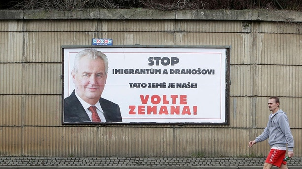 A man walks past a poster promoting the incumbent president Milos Zeman ahead of presidential election run-off in Prague, Czech Republic January 25, 2018. The poster reads: 'Stop migrants and Drahos. This is our land! Vote Zeman!'. REUTERS/David W Cerny - RC1774645580
