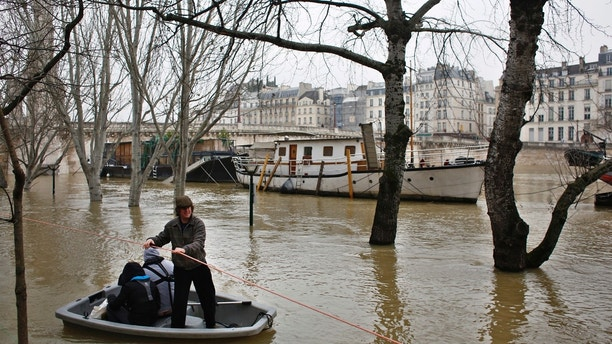 People use a dinghy boat to reach a barge on the river Seine in Paris, Saturday, Jan. 27, 2018. Floodwaters were nearing their peak in Paris on Saturday, with the rain-swollen Seine River engulfing scenic quays and threatening wine cellars and museum basements. (AP Photo/Thibault Camus)