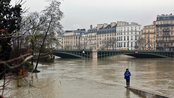 A woman walks along a low wall on the flooded banks of the river Seine in Paris, Saturday, Jan. 27, 2018. Floodwaters were nearing their peak in Paris on Saturday, with the rain-swollen Seine River engulfing scenic quays and threatening wine cellars and museum basements. (AP Photo/Thibault Camus)