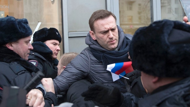 Russian opposition leader Alexei Navalny, centre, is detained by police officers in Moscow, Russia, Sunday, Jan. 28, 2018. Opposition politician Alexey Navalny calls for nationwide protests following Russia's Central Election Commission's decision to ban his presidential candidacy. (AP Photo/Evgeny Feldman)