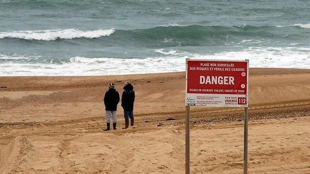 A board signals danger on the beach of Hossegor, southwestern France, during searches for the chief executive of sportswear maker Quiksilver Pierre Agnes, Wednesday, Jan.31, 2018. French authorities have deployed boats and helicopters off the coast of southwest France to search for Agnes after his empty boat was found washed ashore Tuesday. (AP Photo/Bob Edme)