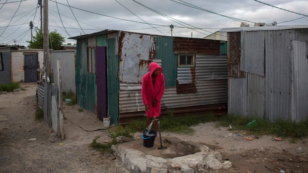 In this Feb. 2, 2018 photo, a woman collects water in a settlement near South Africa's drought-hit city of Cape Town. About a quarter of Cape Town's population lives in the informal settlements, where they get water from communal taps instead of individual taps at home like in the richer suburbs. And they use 4.5 percent of the total water consumption. (AP Photo/Bram Janssen)