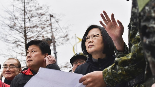 In this photo released by the Taiwan Presidential Office, Taiwan's President Tsai Ing-wen, center, is briefed at the site of a collapsed building from an earthquake, Wednesday, Feb. 7, 2018, in Hualien, southeastern Taiwan. Rescuers continue to search for dozens of unaccounted people for in several buildings damaged by a strong earthquake near the island's eastern coast. (Taiwan Presidential Office via AP)