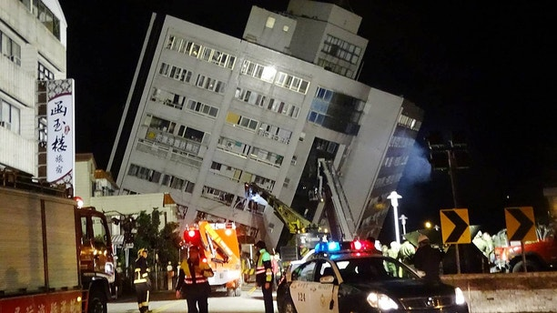 Rescuers are seen entering a building that collapsed onto its side from an early morning 6.4 magnitude earthquake in Hualien County, eastern Taiwan, Wednesday, Feb. 7 2018.  Rescue workers are searching for any survivors trapped inside the building. (AP Photo/Tian Jun-hsiung)