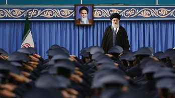 In this picture released by official website of the office of the Iranian supreme leader, Supreme Leader Ayatollah Ali Khamenei stands as army air force and air defense staff salute at the start of their meeting in Tehran, Iran, Thursday, Feb. 8, 2018. A portrait of the late revolutionary founder Ayatollah Khomeini hangs in background. (Office of the Iranian Supreme Leader via AP)