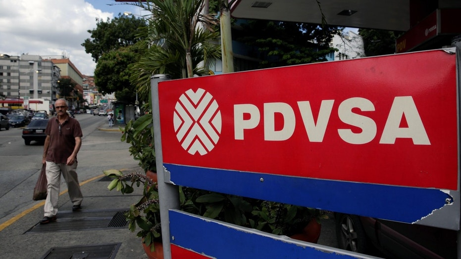 A man walks past the corporate logo of the state oil company PDVSA at a gas station in Caracas, Venezuela December 1, 2017. REUTERS/Marco Bello - RC1F873E1C20