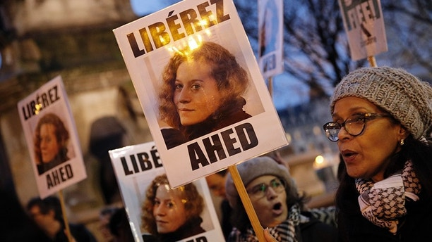 "FILE - In this Jan. 4, 2018 file photo, demonstrators hold posters reading, ""Release Ahed"" during a protest demanding Israel to release Ahed Tamimi. Tamimi is to go on trial Tuesday, Feb. 13, 2018, before an Israeli military court, for slapping and punching two Israeli soldiers in December. Palestinians say her actions embody their David vs. Goliath struggle against a brutal military occupation, while Israel portrays them as a staged provocation meant to embarrass its military. Tamimi is one of an estimated 350 Palestinian minors in Israeli jails. (AP Photo/Christophe Ena, File)"