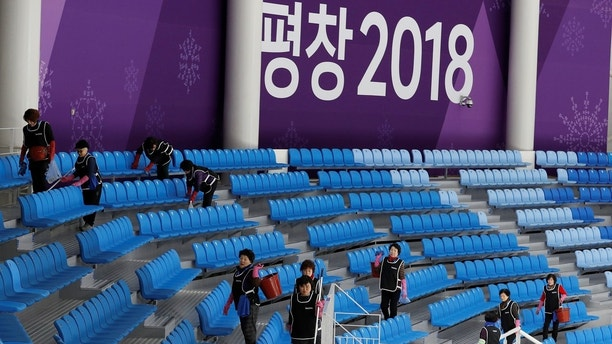 Speed Skating - Pyeongchang 2018 Winter Olympics - Training - Gangneung Oval, Gangneung, South Korea - February 7, 2018 Cleaning staff make final tidy the spectator seating area. REUTERS/Phil Noble - RC1CB39D3960