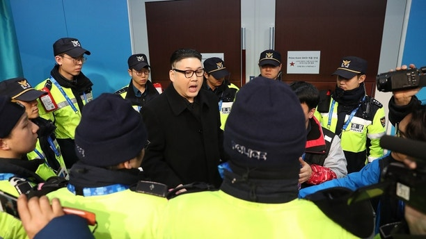 Ice Hockey – Pyeongchang 2018 Winter Olympics – Women Preliminary Round Match - Korea v Japan - Kwandong Hockey Centre, Gangneung, South Korea – February 14, 2018 - Kim Jong-un impersonator is surrounded by security personnel. REUTERS/Lucy Nicholson - HP1EE2E0TCLLK