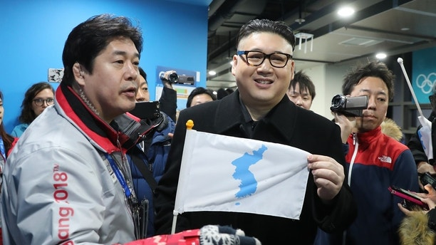Ice Hockey – Pyeongchang 2018 Winter Olympics – Women Preliminary Round Match - Korea v Japan - Kwandong Hockey Centre, Gangneung, South Korea – February 14, 2018 - Kim Jong-un impersonator holds a Korean unification flag. REUTERS/Lucy Nicholson - HP1EE2E0THFLQ