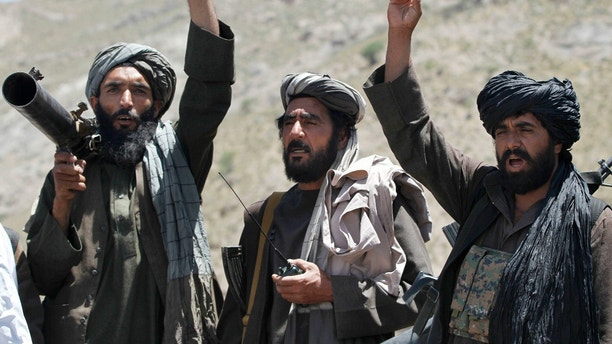 FILE - In this May 27, 2016 file photo, Taliban fighters react to a speech by their senior leader in the Shindand district of Herat province, Afghanistan. After operating out of Pakistan for more than a decade, the leaders of Afghanistan's Taliban movement may have moved back to their homeland to try to build on this year's gains in the war and to establish a permanent presence. If confirmed, the move would be a sign of the Taliban's confidence in their fight against the U.S.-backed government in Kabul. (AP Photos/Allauddin Khan, File)