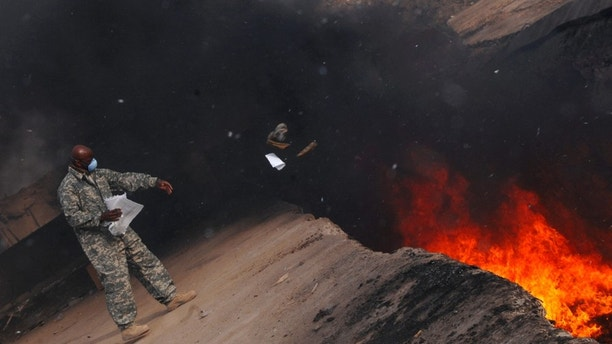 Master Sgt. Darryl Sterling, 332nd Expeditionary Logistics Readiness Squadron equipment manager, tosses unserviceable uniform items into a burn pit here, March 10. The 332 ELRS has a central collection point that can be used by service members and Department of Defense civilians; unserviceable uniform items are burned. Sergeant Sterling is deployed from Luke Air Force Base, Ariz.