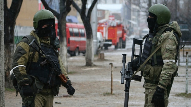 Members of Russia's special forces stand guard during an operation on suspected militants in Makhachkala, the capital of Russia's North Caucasus Republic of Dagestan January 20, 2014. An Islamic militant group said in a video posted online that it was behind two suicide bombings that killed at least 34 people last month in the Russian city of Volgograd, and threatened to attack the Sochi Winter Olympics. The video says two men called Suleiman and Abdurakhman carried out the Volgograd attacks on behalf of a group known as Vilayat Dagestan and linked to an Iraqi faction called Ansar al-Sunna.  REUTERS/Stringer  (RUSSIA - Tags: POLITICS CIVIL UNREST MILITARY) - GM1EA1K1SZ601
