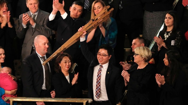 North Korean defector Ji Seong-ho, currently a law student at Dongguk University, holds up his crutches as he is ackowledged by U.S. President Donald Trump during his State of the Union address to a joint session of the U.S. Congress on Capitol Hill in Washington, U.S. January 30, 2018. REUTERS/Carlos Barria - HP1EE1V0BIB29