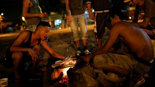Men cook arepas using firewood in a sport center where a community of homeless Venezuelan migrants stays, in Cucuta, Colombia January 23, 2018. Picture taken January 23, 2018. REUTERS/Carlos Garcia Rawlins - RC147F2ED7B0