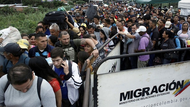 People queue to try to cross into Venezuela from Colombia through the Simon Bolivar international bridge in Cucuta, Colombia February 13, 2018. REUTERS/Carlos Eduardo Ramirez - RC155A4D8060
