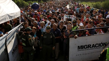 Colombian police officers stand in front of people queueing to try to cross into Colombia from Venezuela through Simon Bolivar international bridge in Cucuta, Colombia January 24, 2018. REUTERS/Carlos Garcia Rawlins - RC1B1A482AB0