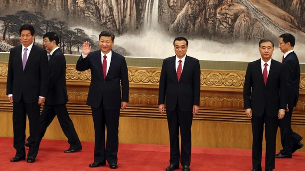 FILE - In this Oct 25, 2017, file photo, Chinese President Xi Jinping, third from left, waves near Chinese Premier Li Keqiang, third from right, as they walk in with other members of the Chinese Politburo Beijing's at the Great Hall of the People. On a proposal made public Sunday, Feb. 25, 2018, China's ruling Communist Party proposes removing a limit of two consecutive terms for the president and vice president. (AP Photo/Ng Han Guan, File)
