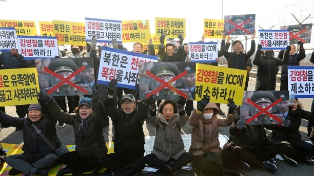 "Family members of victims of the sunken South Korean naval ship Cheonan by a North Korean attack hold up defaced portraits of Kim Yong Chol, vice chairman of North Korea's ruling Workers' Party Central Committee, during a rally against his visit near the Unification bridge in Paju, South Korea, Sunday, Feb. 25, 2018. A North Korean high-level delegation led by Kim arrived to attend the closing ceremony of the Pyeongchang Winter Olympics. The signs read: "" Let's punish Kim Young Chol."" (AP Photo/Ahn Young-joon)"
