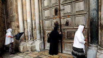 Worshippers stand in front of the closed doors of the Church of the Holy Sepulchre in Jerusalem's Old City February 26, 2018. REUTERS/Ronen Zvulun - RC13237EB990