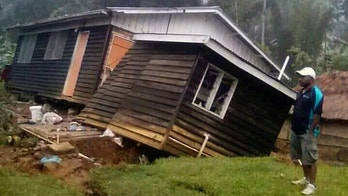 A man views a house that collapsed in a strong earthquake, Tuesday, Feb. 27, 2018, in Halagoli, Hela Province, Papua New Guinea. Severe damage after Monday's powerful 7.5 magnitude earthquake in Papua New Guinea is hindering efforts to assess the destruction, although officials fear dozens of people may have been injured or killed. (Jerol Wepii via AP)