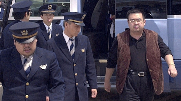 A man (R) believed to be North Korean heir-apparent Kim Jong Nam, is escorted by police as he boards a plane upon his deportation from Japan at Tokyo's Narita international airport in Narita, Japan, in this photo taken by Kyodo May 4, 2001. Picture taken May 4, 2001. Mandatory credit Kyodo/via REUTERS ATTENTION EDITORS - THIS IMAGE WAS PROVIDED BY A THIRD PARTY. EDITORIAL USE ONLY. MANDATORY CREDIT. JAPAN OUT. NO COMMERCIAL OR EDITORIAL SALES IN JAPAN. - RC11E3489C60