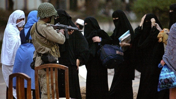 Radical Muslim female students surrender themselves to soldiers near Lal Masjid or Red Mosque in Islamabad July 4, 2007. The head of a radical Pakistani mosque at the centre of a stand-off with security forces was arrested on Wednesday while trying to escape clad in a woman's burqa, officials said.  REUTERS/Mian Khursheed  (PAKISTAN) - GM1DVQAGXTAA