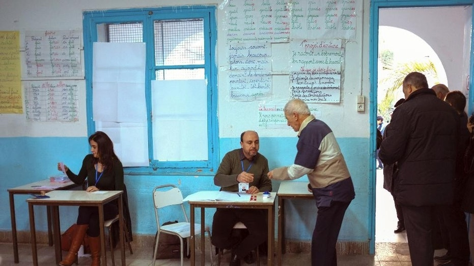 Tunisians check voter IDs in a polling station in Tunis, Tunisia, back in 2014.