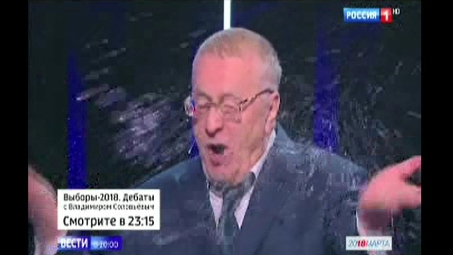 Vladimir Zhirinovsky, the 71-year-old leader of the ultranationalist Liberal Democratic Party, has water thrown at him during Wednesday night's presidential debate.