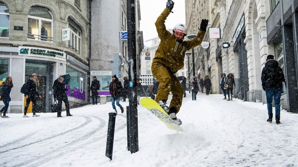 Sylvain rides  his snowboard on a snow-covered street during a snowfall in Lausanne, Switzerland, Thursday, March 1, 2018. (Jean-Christophe Bott/Keystone via AP)