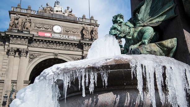 The icy Alfred Escher fountain is pictured in Zurich, Switzerland, Wednesday, Feb. 28, 2018.  An extreme Siberian cold snap sweeping across Europe is claiming lives in Poland and Romania, but also dusted the ancient ruins of Pompeii with snow Tuesday and prompted Amsterdam authorities to prepare the city's iconic canals for ice-skaters. (Melanie Duchene/Keystone via AP)